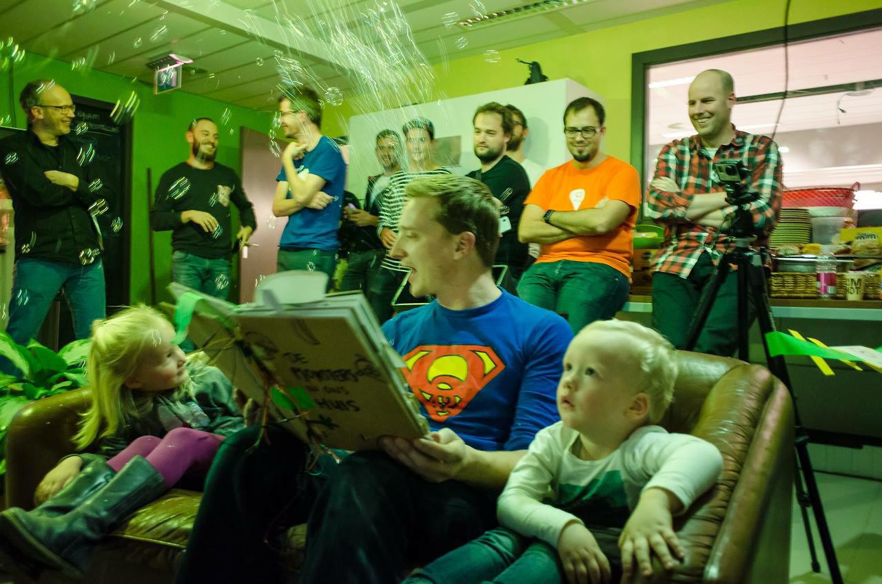 Vader en z'n twee kinderen op de bank tijdens een demo van het connected voorleesboek tijdens een hackathon