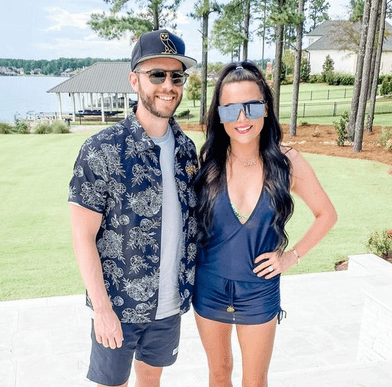 Adrian Morrison and his wife with a lake backdrop