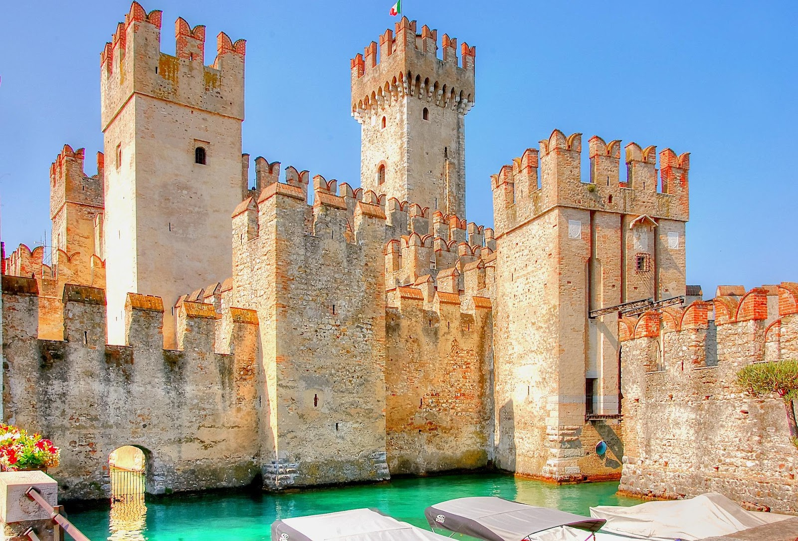 sirmione scalgiero whitewashed bright medieval castle fortress with blue moat italy clear day