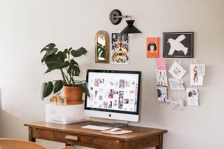 počítač na drevenom stole s črepníkovou rastlinou a dekoráciami na stene