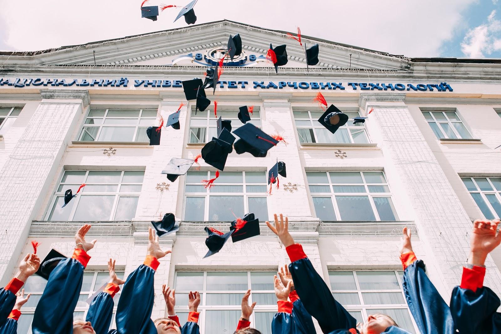 Graduates throwing caps in the air.