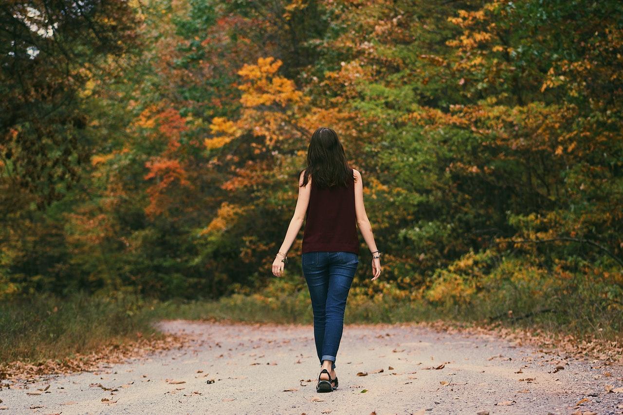 Eine Frau, die im Herbst in einem Park geht