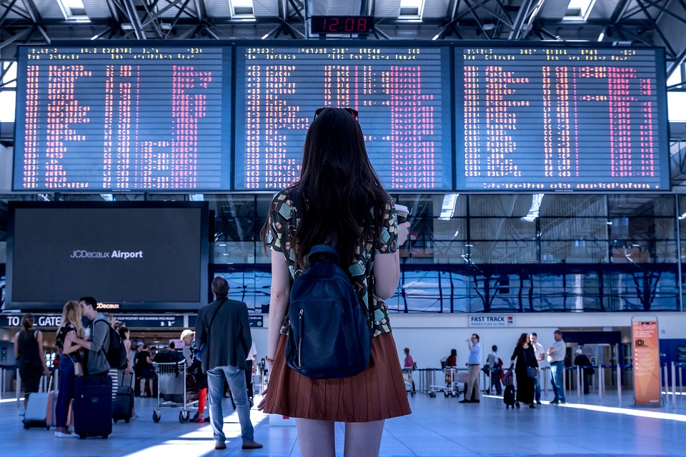 A lady looking at a flight screen fiinding her flight details at the airport