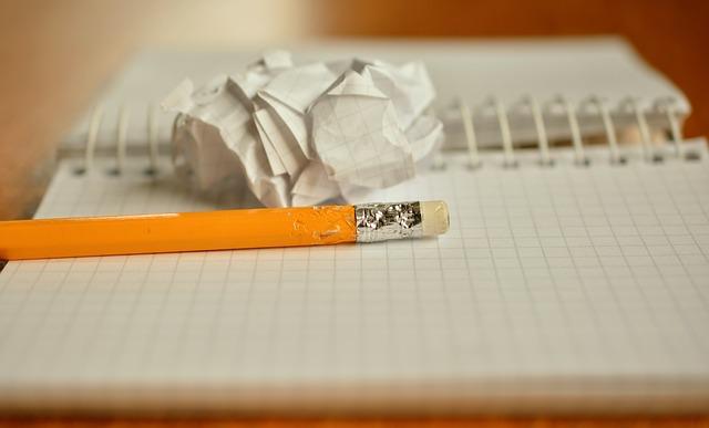 imagem lápis, caderno e papel amassado