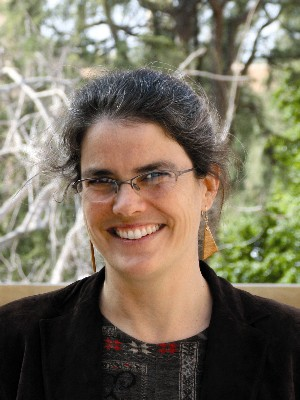 Image of Professor Andrea Ghez; a woman with dark hair and streaks of grey, glasses, and a black blazer