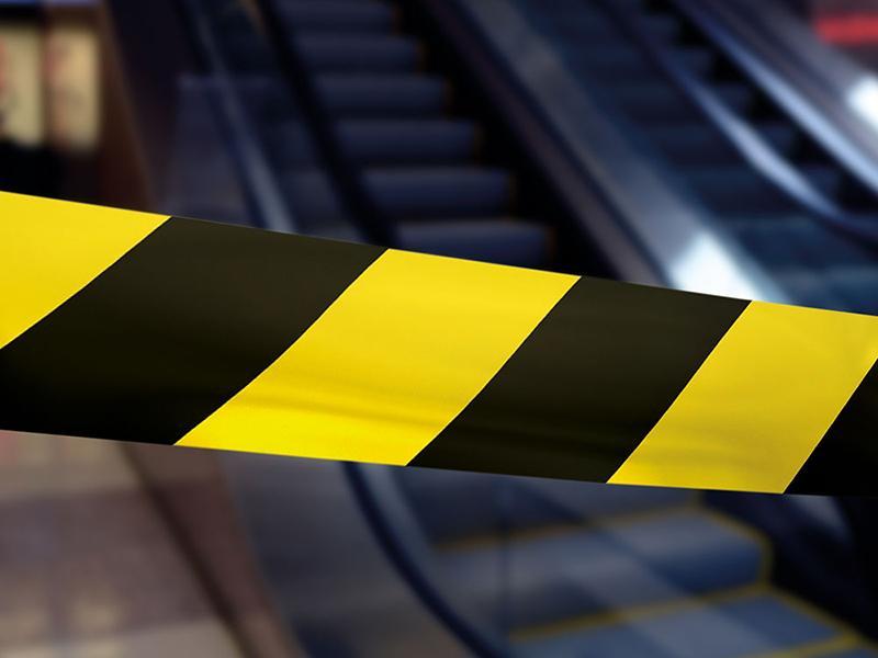 A imagem mostra uma fita isolando uma escada rolante ao fundo, é uma proteção na reabertura