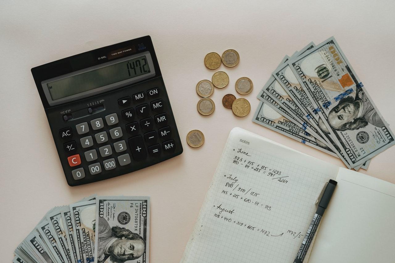Pieniądze, kalkulator, notes i długopis na białym stole