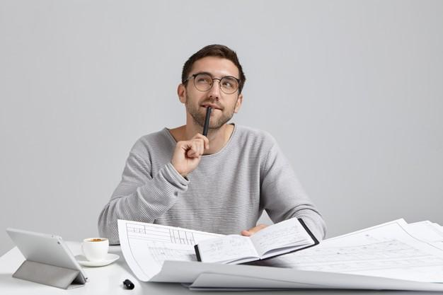 Young man sitting at desk and doing paperwork Free Photo