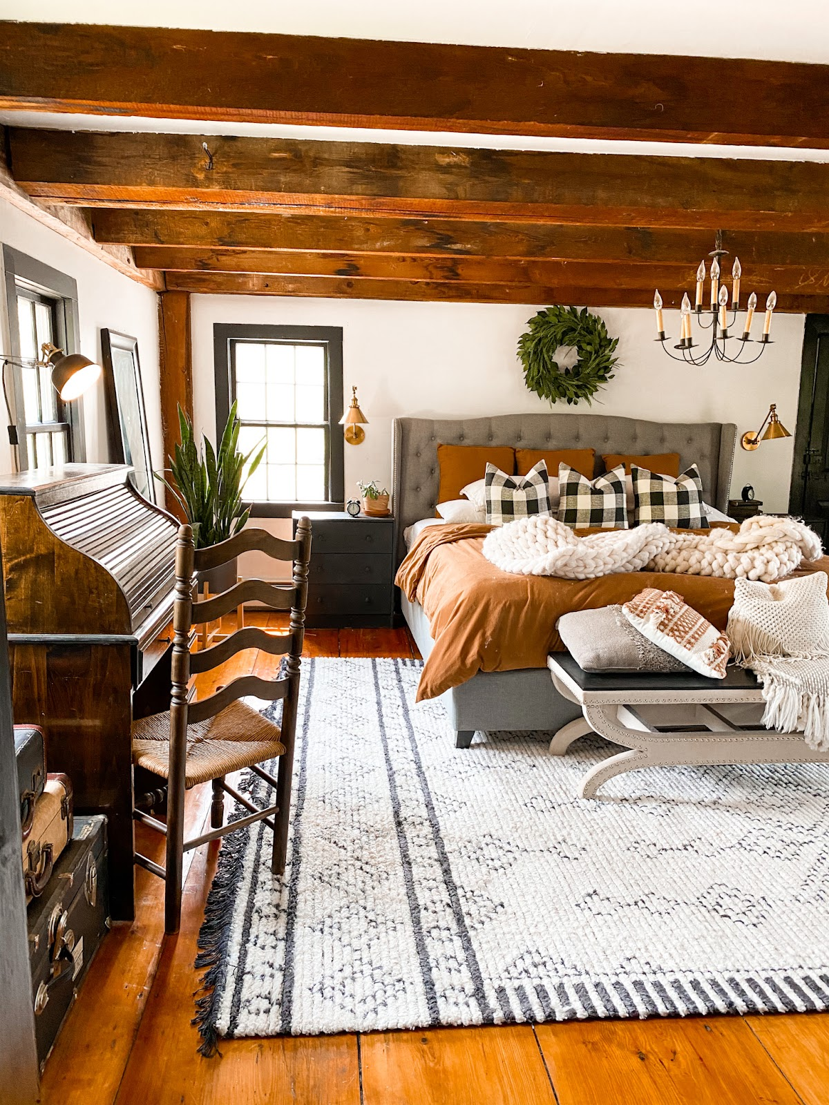 boho bedroom with rust bedding, an exposed beamed ceiling, and green plants