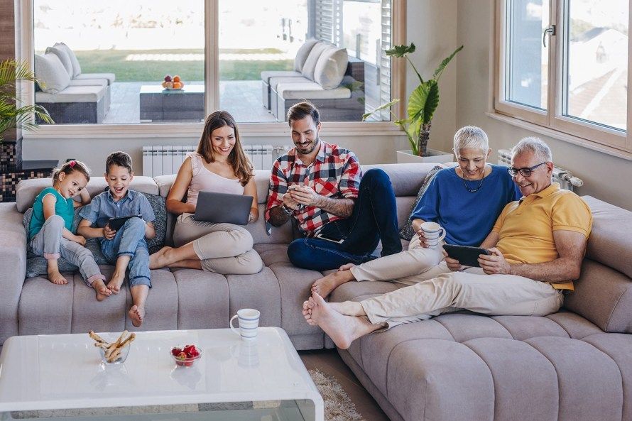 two kids, their parents, and grandparents relaxing on a sectional couch