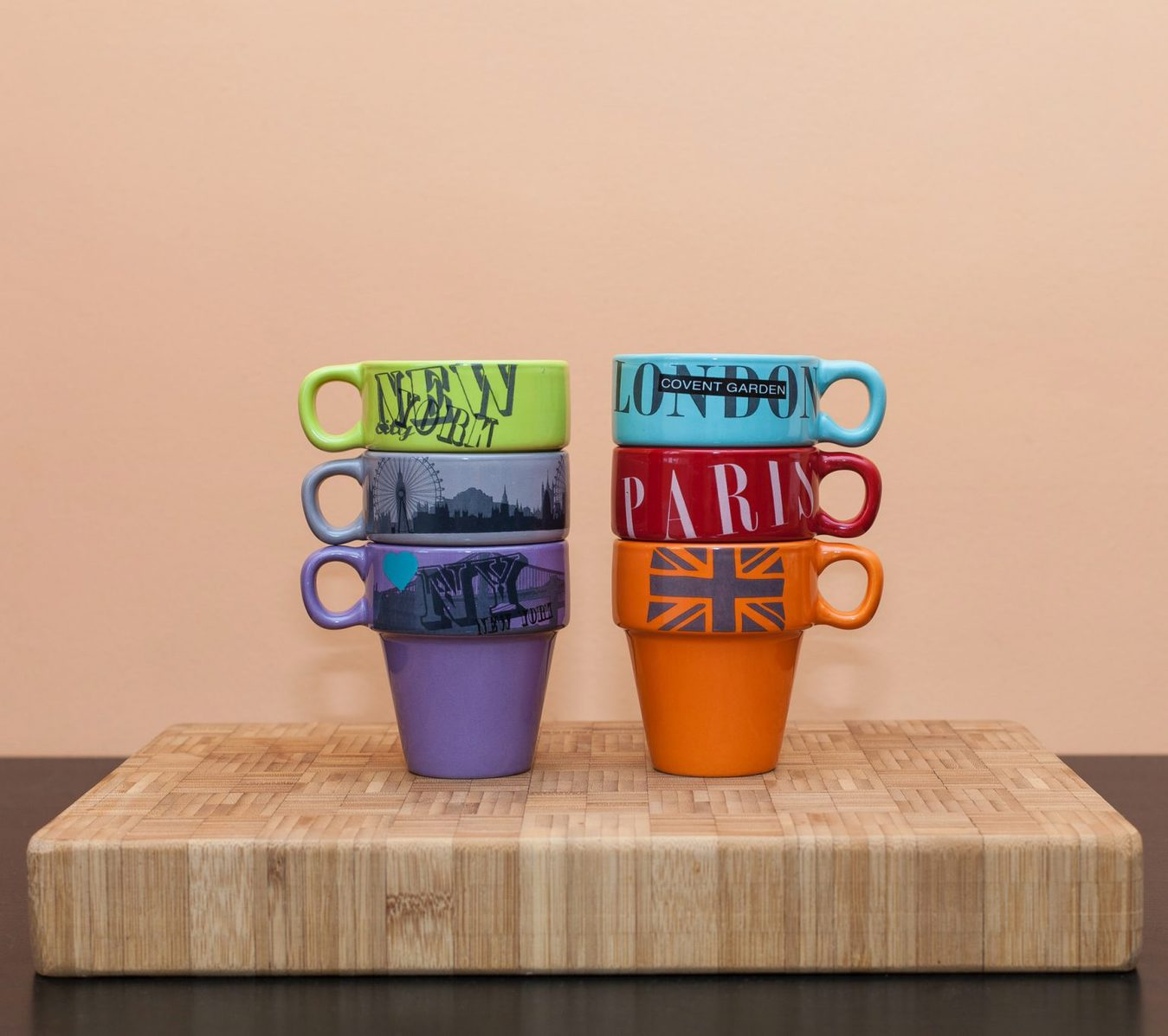 Stacked up mugs against a peach background