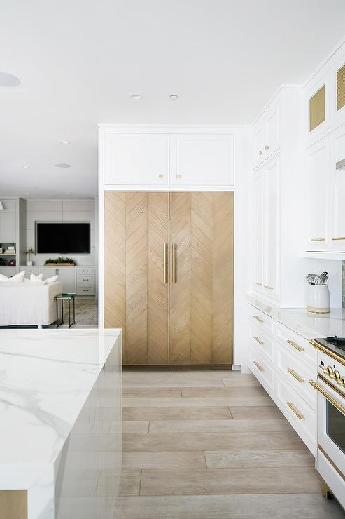 white and gold kitchen with wooden fridge. fridge doors have a herringbone pattern and gold bar pulls