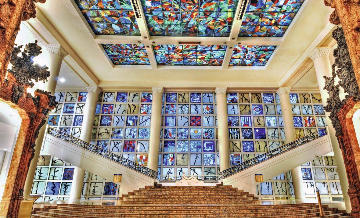 Vista interna do Museu em SP de Arte Brasileira, com escadaria, para direita e para esquerda, e paredes formadas por azulejos coloridos.