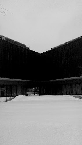 A dark black structure stands on a snowed landscape