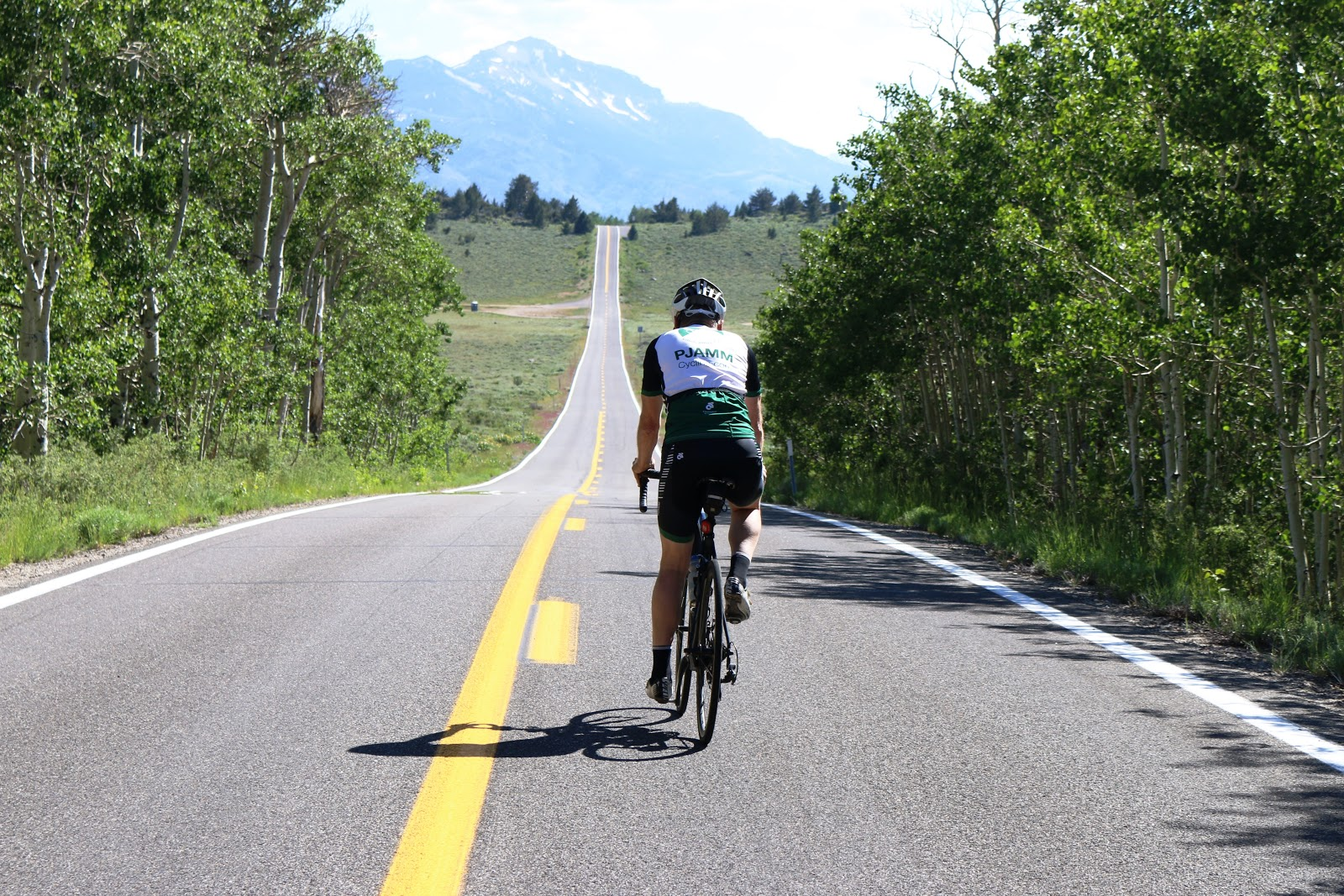 Cycling Monitor Pass East  - bicyclist riding west as the pass - roadway and mountains
