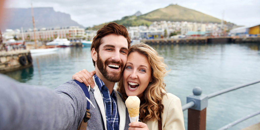 Happy couple traveling and eating ice cream