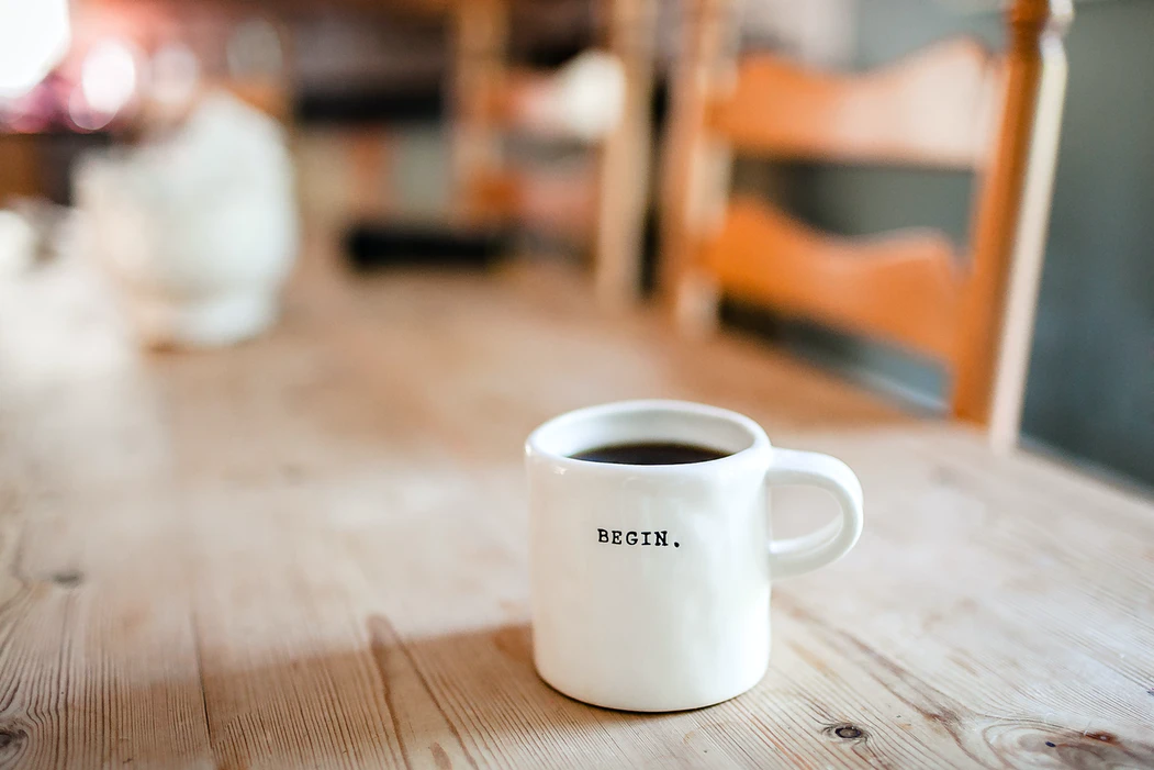 Close up of a white ceramic mug with the word BEGIN written on it. It sits on top of a wooden table.