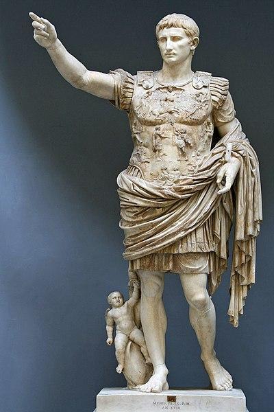 Standing statue of Augustus Caesar in Roman armor with upraised arm.