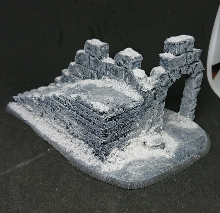 A completed terrain piece of a ruin with snow effects.