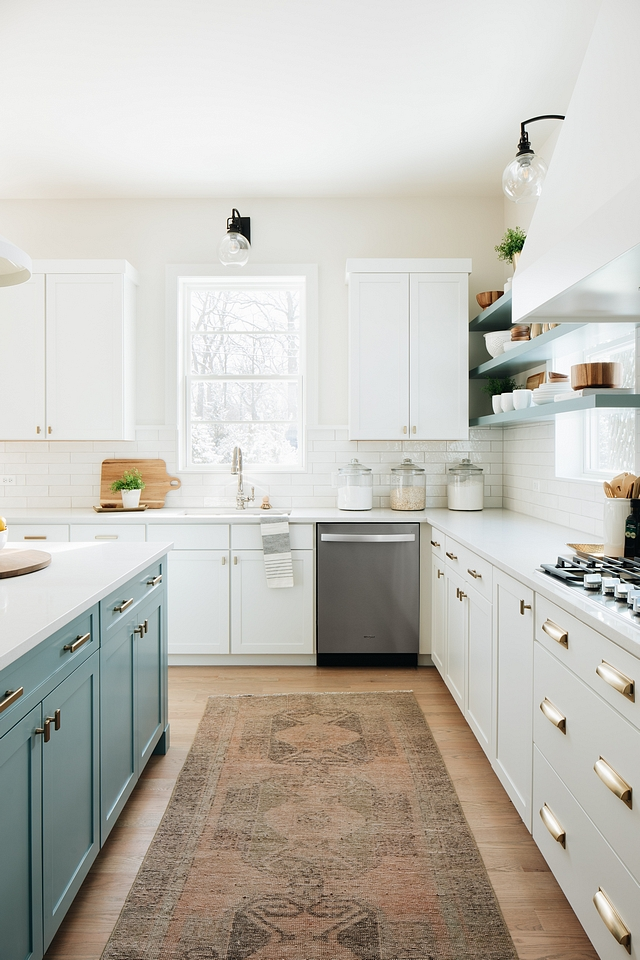 blue cabinets on the kitchen island make it stand out against the white cabinetry in the rest of the kitchen. the two toned look with blue and white cabinets evokes a coastal charm