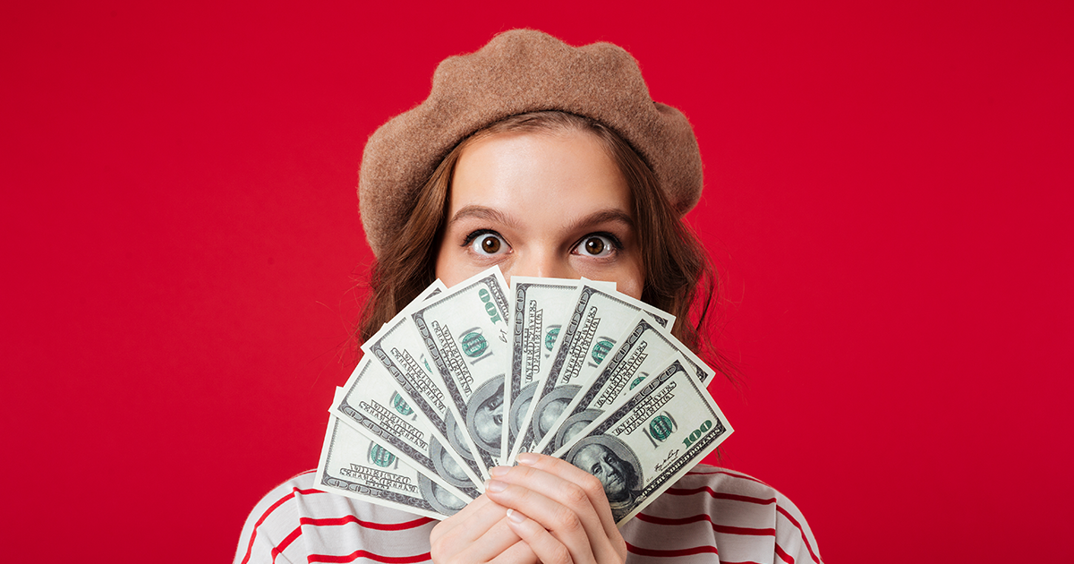girl holding money in front of her face
