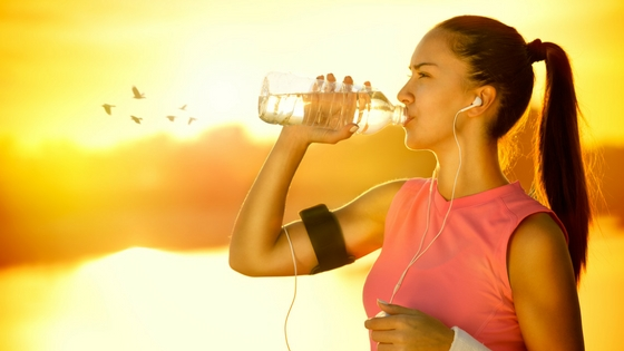 woman in exercise clothing drinking water with sunset in the background