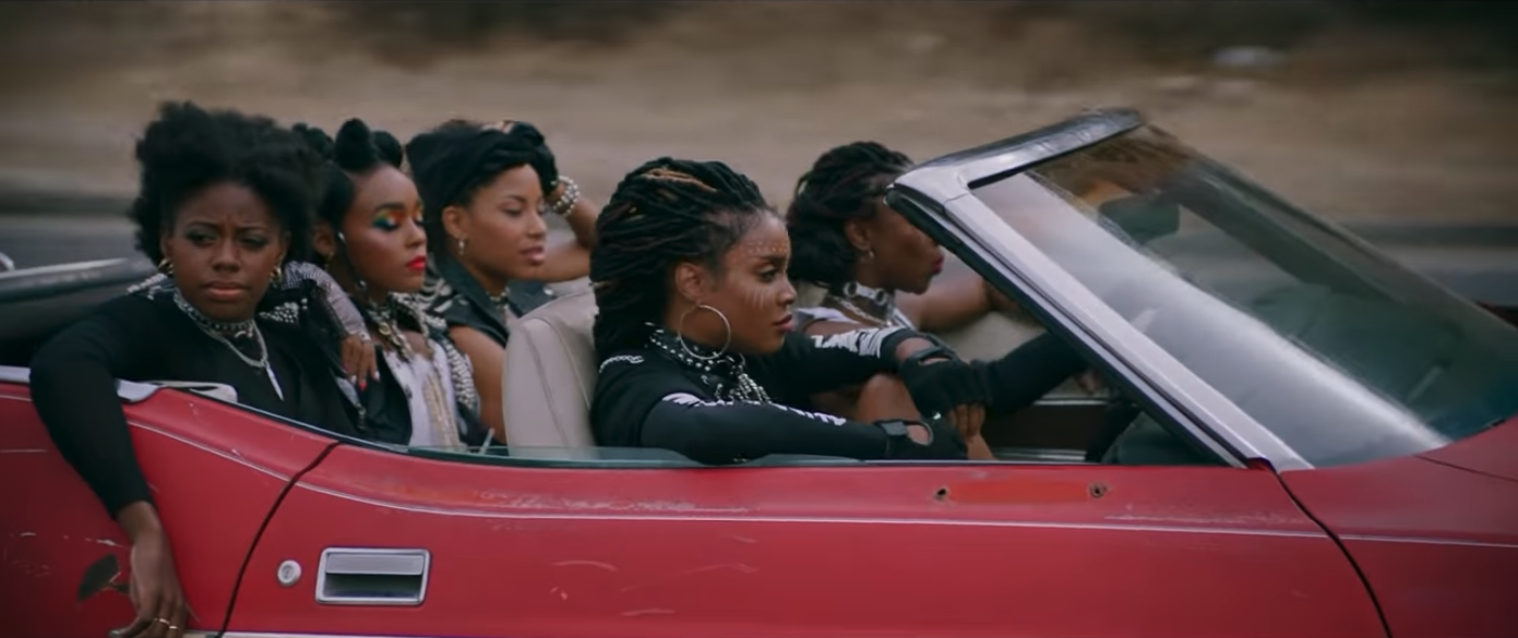 Five Black women in a red convertible hovercar.