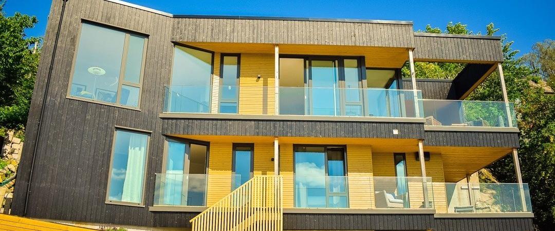 Moderne hus med mange vinduer, bygget av byggmestere, bygg hus med våre beste byggmestere