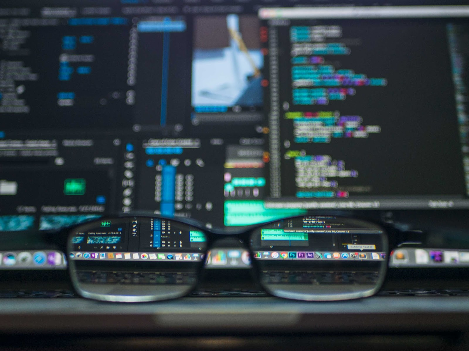 Recent data breaches: Glasses sat on desk in front of a computer monitor showing code.