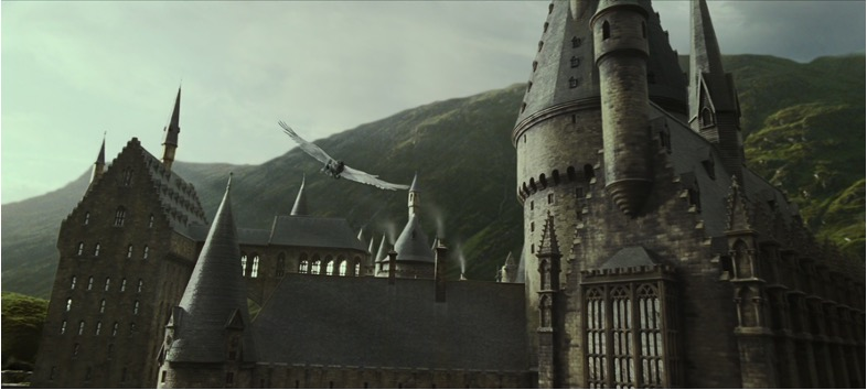Still from Harry Potter and the Deathly Hallows, Part 2. A sweeping wide shot of Hogwarts castle in the daylight, as an owl swoops over the rooftops and turrets.