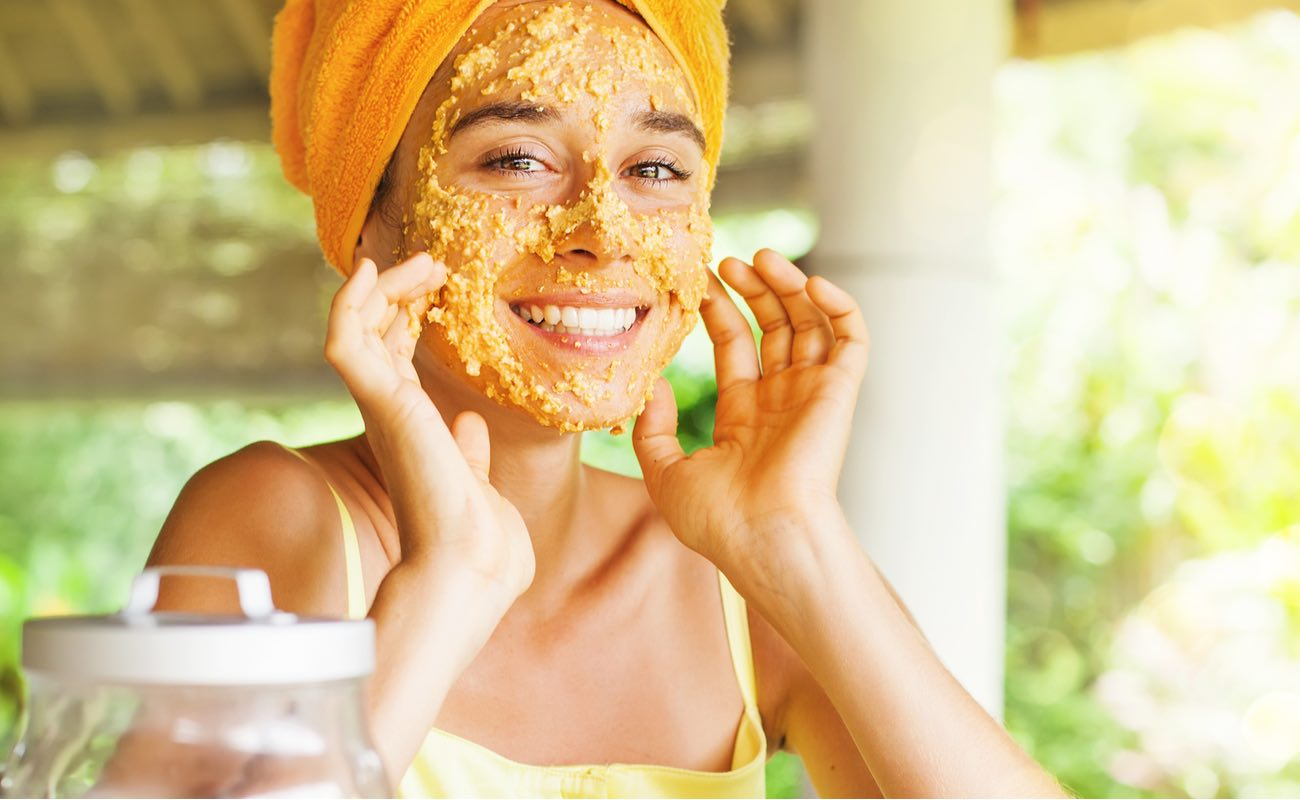 Smiling woman with oatmeal mask on face, blurred nature in background