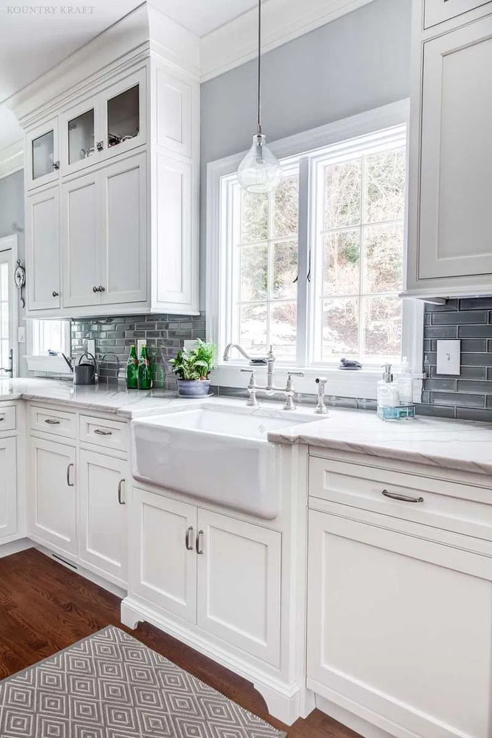 white traditional kitchen with white shaker cabinets, chrome bar pulls, grey backsplash and large white farmhouse sink