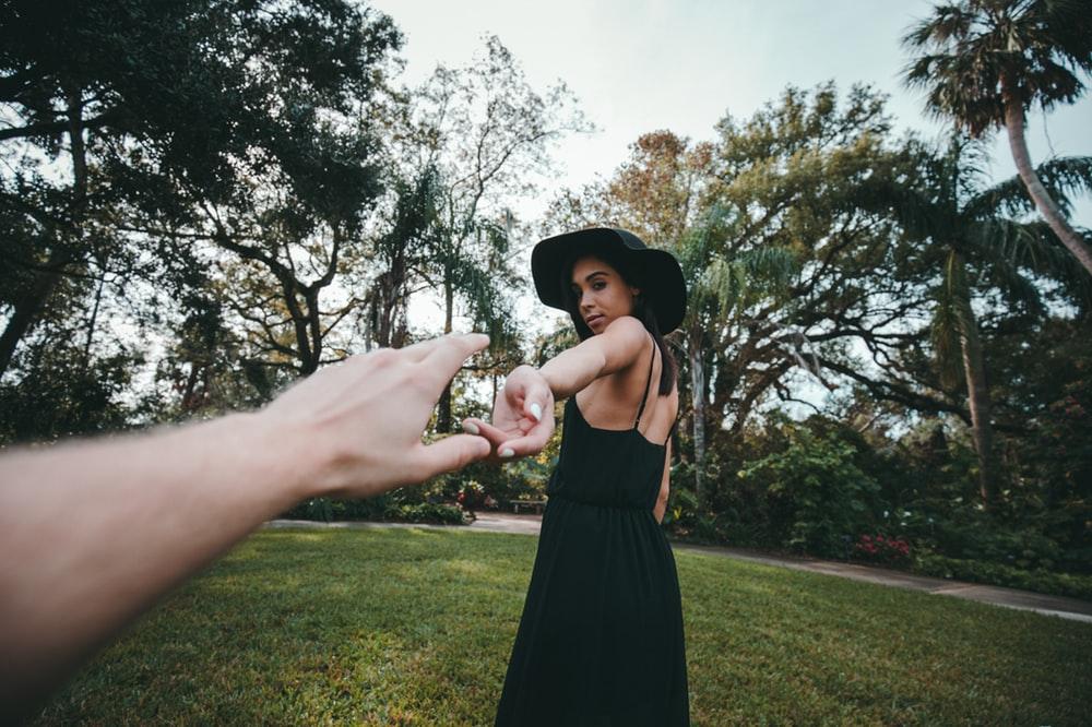 person reaching woman's hand wearing black spaghetti strap dress standing on green grass
