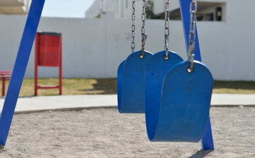 Blue swing set in an empty playground