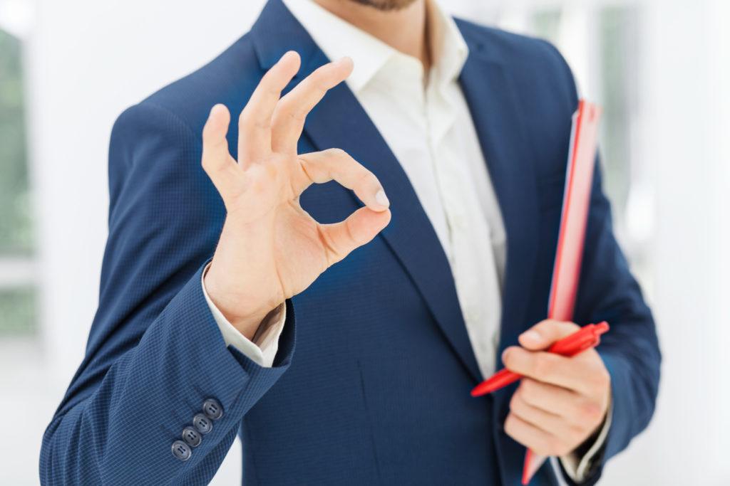 courtier immobilier en veston bleu et chemise blanche avec des dossiers immobiliers dans la bas et une autre main tendue devant lui faisant le signe ok à montréal