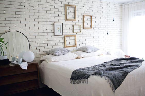 Quarto com cama de casal, parede da cabeceira com azulejo subway tiles branco, quadros com molduras douradas, criado mudo de madeira escura e espelho redondo.