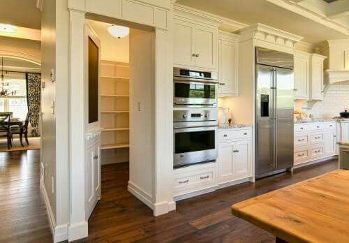 door opening to hidden pantry in large white kitchen with wood floors and stainless steel appliances