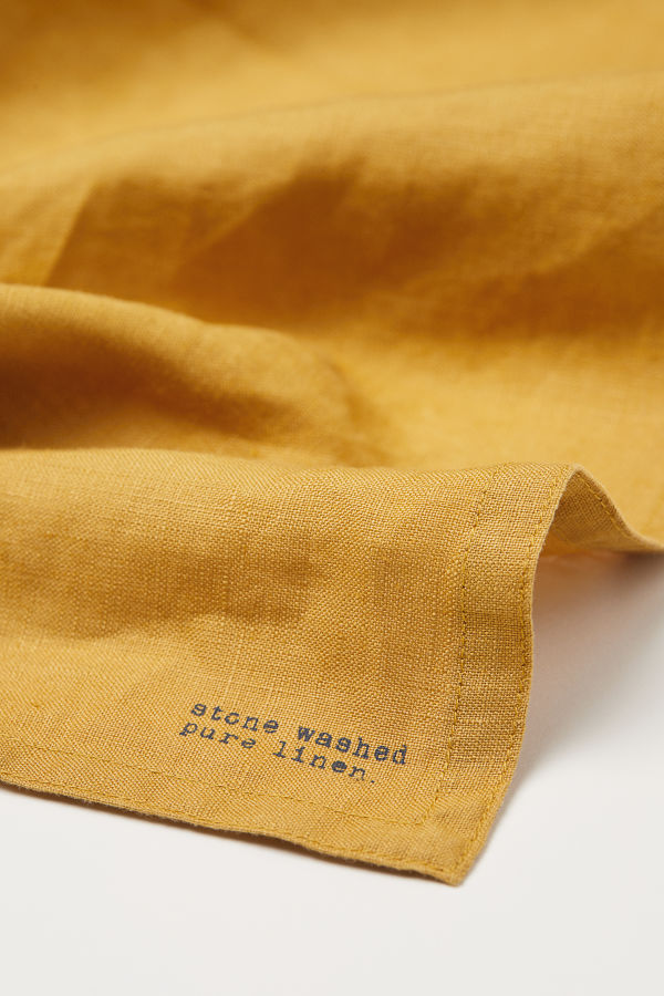 "Yellow napkin with ""stone washed pure linen"" text"