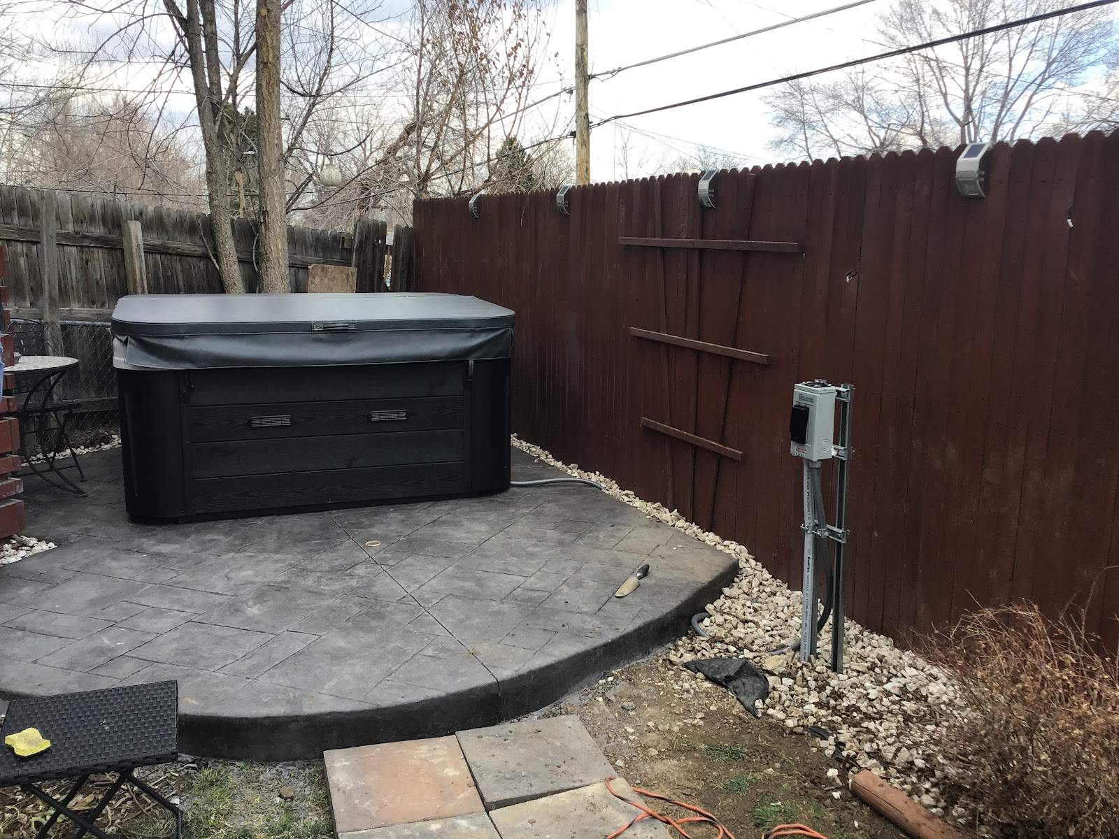 new hot tub with cover, installed on concrete patio in corner of yard where two fences meet, plus freestanding safety disconnect