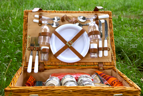 Pictured: a fully stocked wicker picnic basket opened to show all the goodies.
