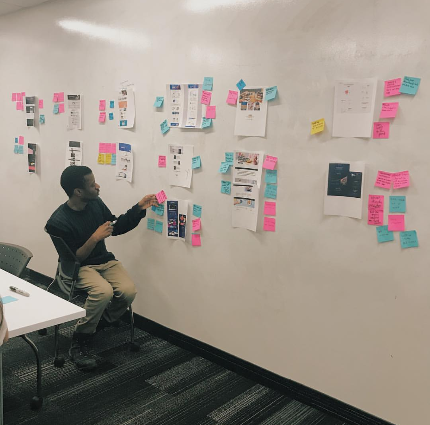 Mackenzie Derival working on a UX project in a design studio setting.
