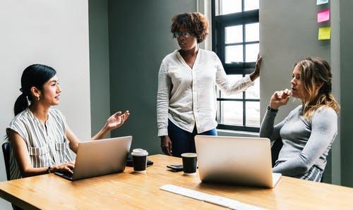 Three Woman Talking Near Laptop on Desk Inside Room