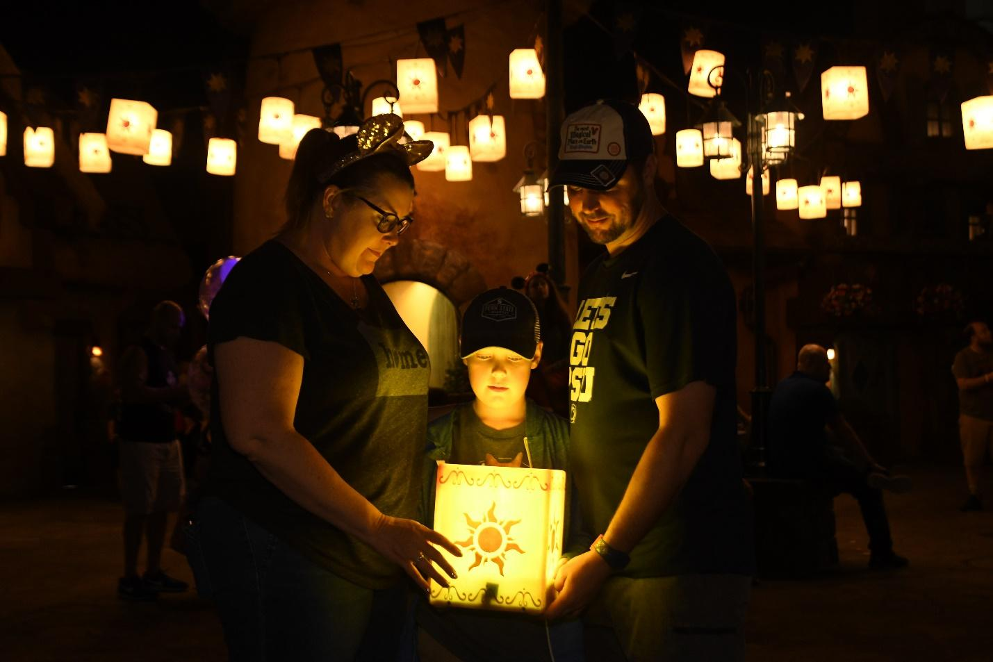 Disney's Memory Maker photo captures a family enjoying the warm glow of Tangled lantern light.