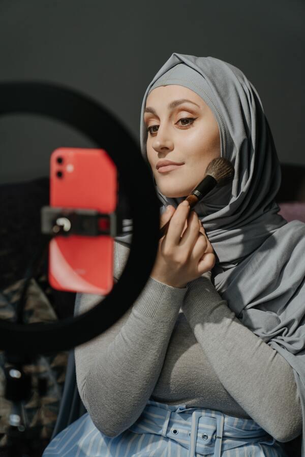 mulher fazendo tutorial de maquiagem com o celular gravando