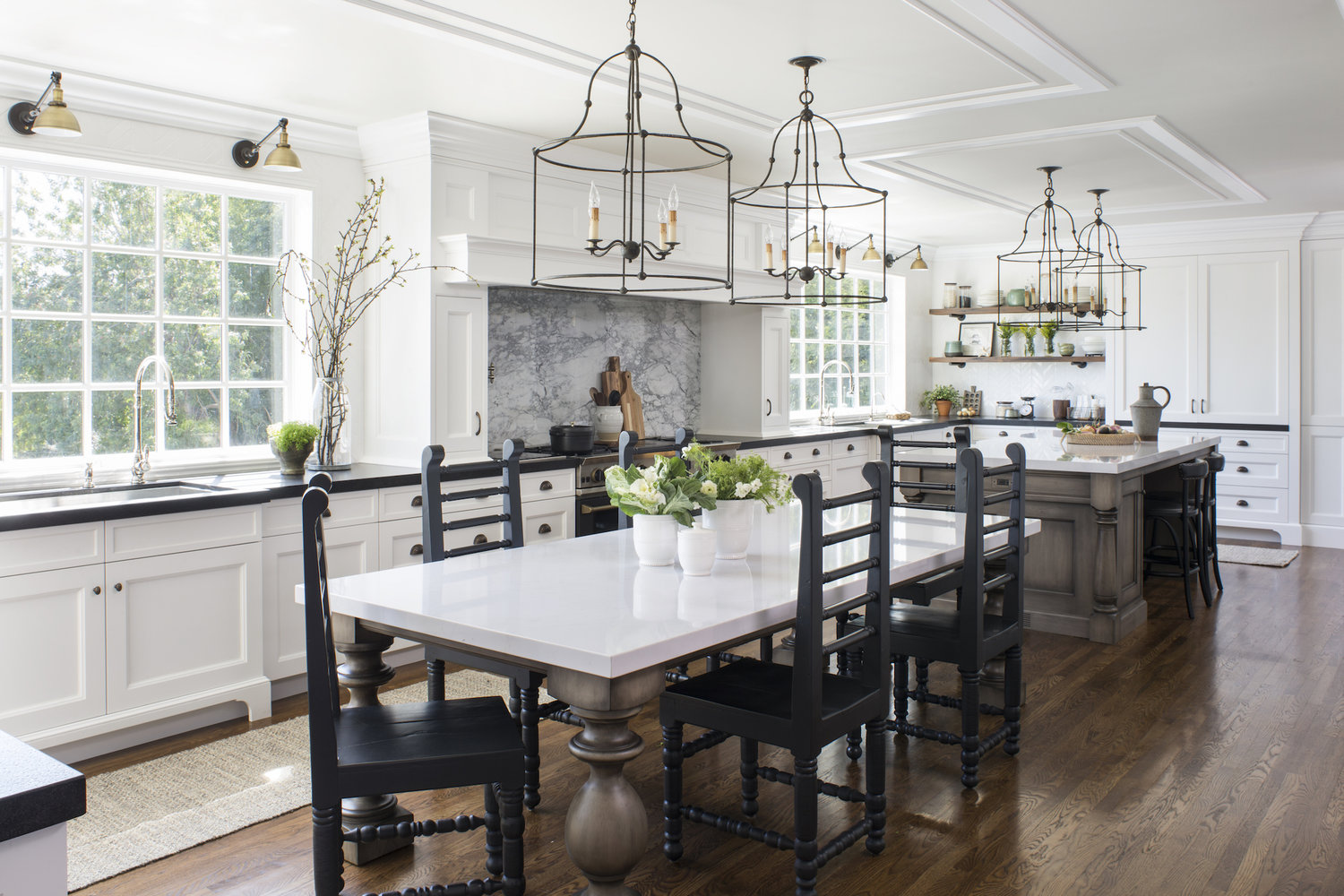 large coastal kitchen design with white cabinets and black countertops. a large center island and dining table with white marble top occupy the center of the kitchen. black pendant lights hang above surrounded by crown molding on the ceiling