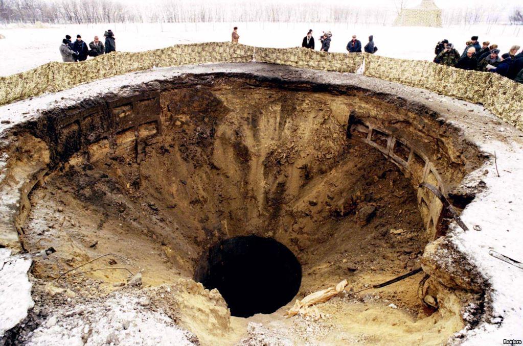 Журналісти та офіційні особи зі США, Росії та України оглядають воронку після вибуху пускової установки на базі в Первомайську в 1996 році. У червні 1996 року Україна перевезла в Росію останні 40 ядерних боєголовок і офіційно стала без'ядерною державою