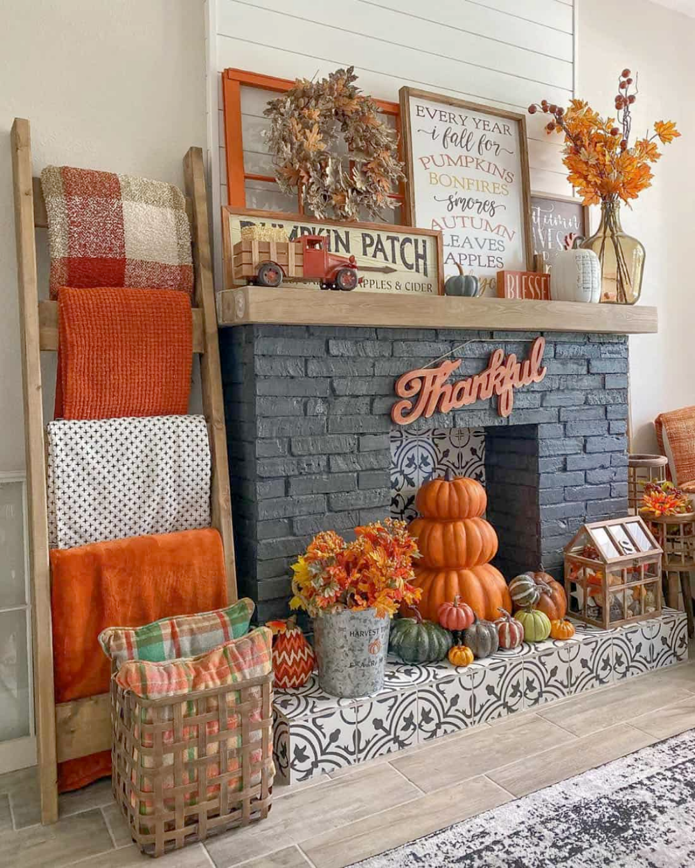Fall inspired mantel black brick fireplace with orange, green, red pumpkins. and sign that reads Thankful and fall colored leaves oranges and reds in vases and a vintage can. Different shades of oranges blankets on a ladder hanger.
