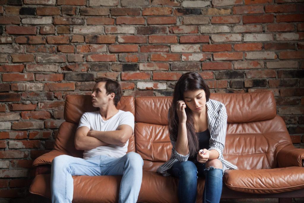 un homme et une femme tristes ou fâchés assis sur un canapé de cuir brun devant un mur de brique réfléchissant au divorce dans leur maison de montréal