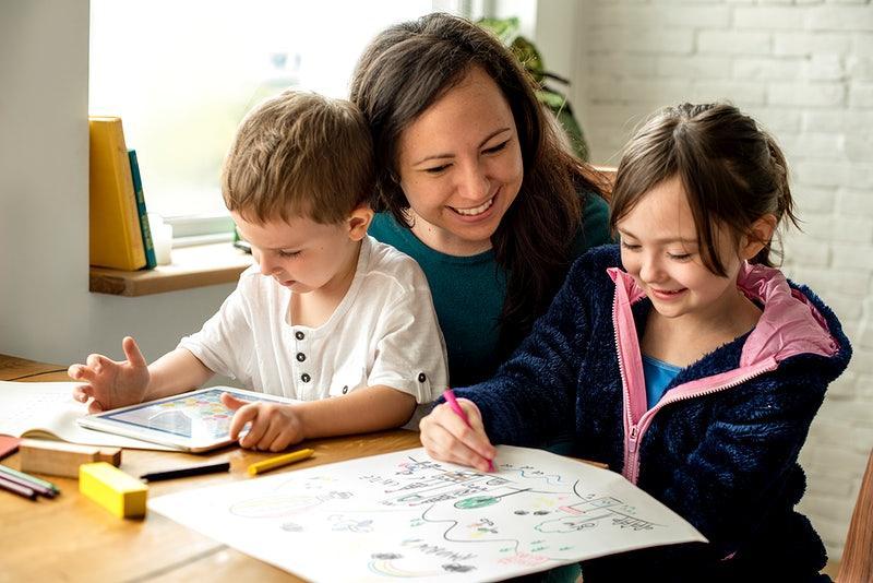 Crianças fazendo suas atividades escolares junto com sua mãe