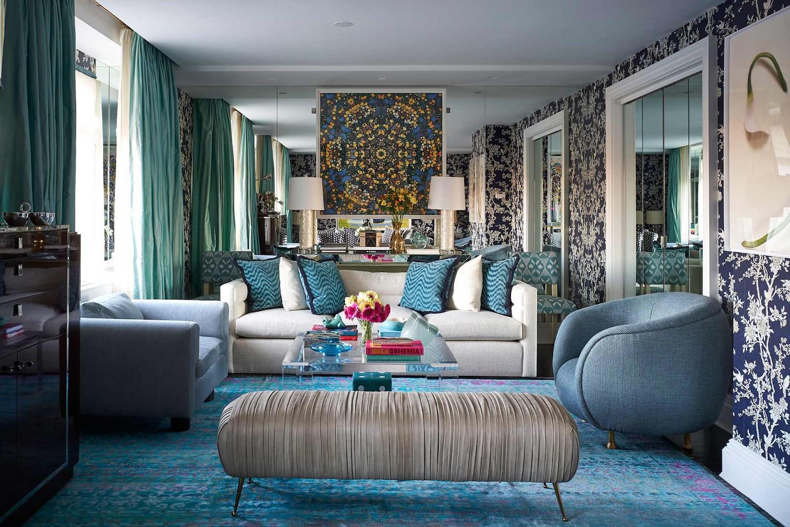 Ambiente com tapete azul e poltronas azuis, sofá banco com almofadas.